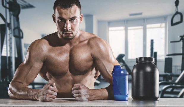 Muskulöser Mann sitzt schwitzend in Fitnesshalle mit Trinkbecher und Supplement.